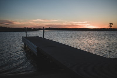 brown wooden dock on body of water north dakota zoom background