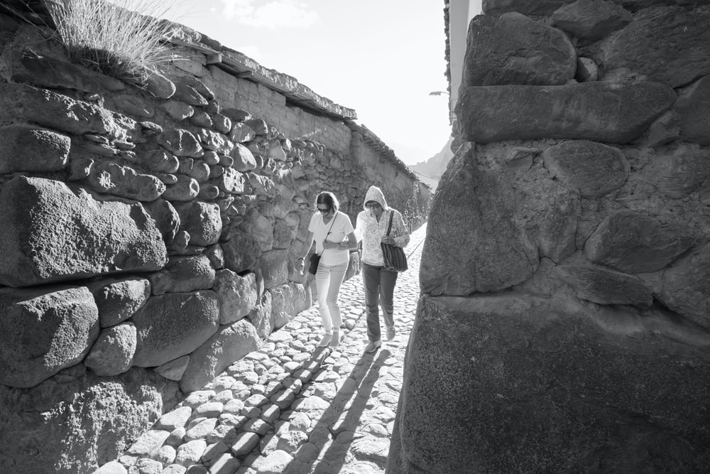 grayscale photography of two women walking along a narrow pathway