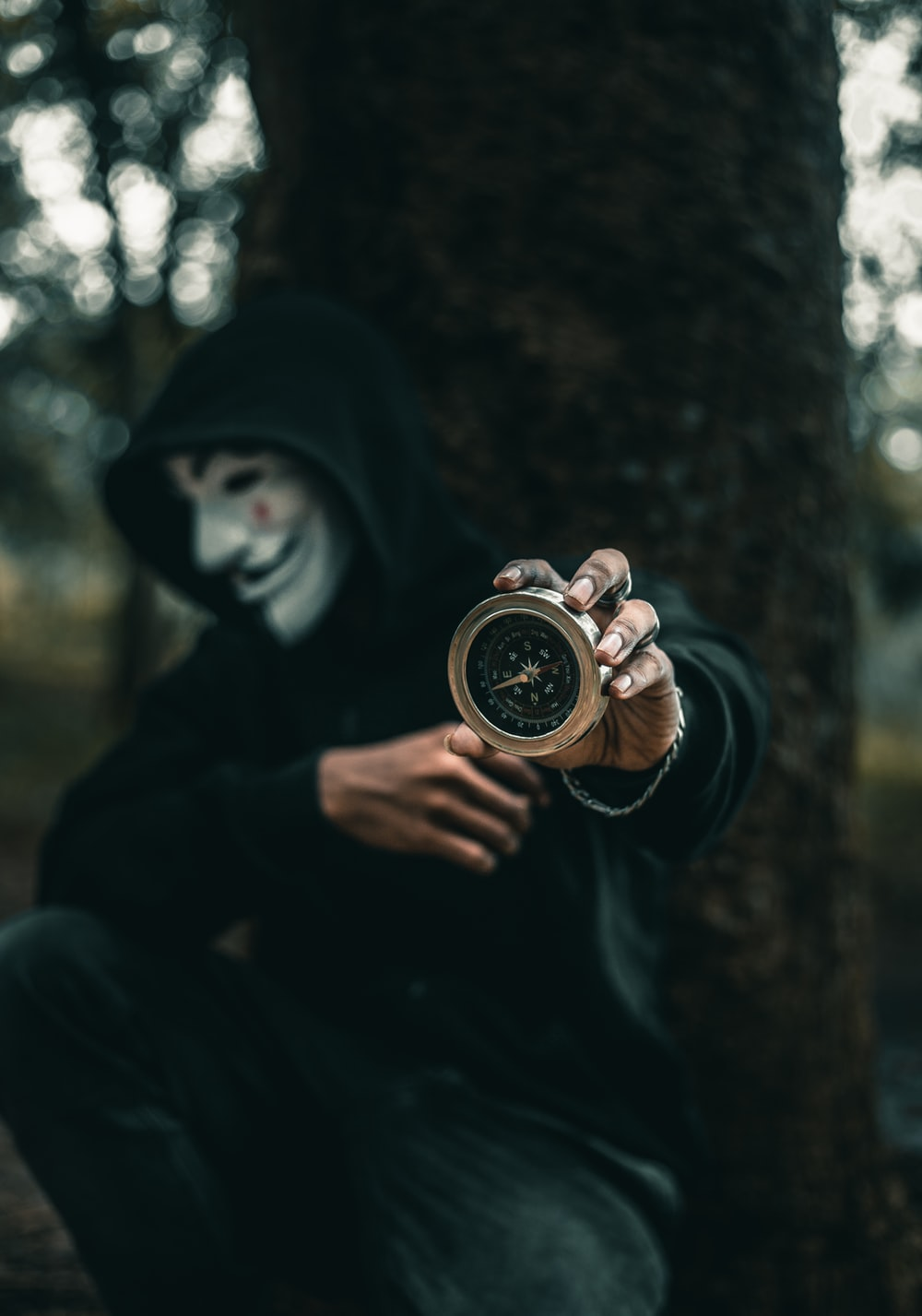 person wearing Guy Folkes mask holding round gold-colored compass