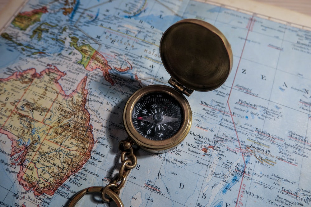 round brass-colored compass on map