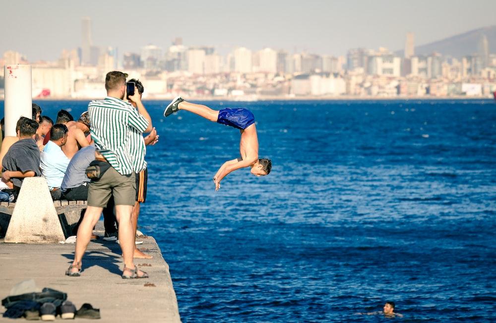 man wearing blue shorts diving during daytime