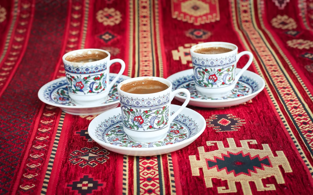 three multicolored floral ceramic cups and saucers
