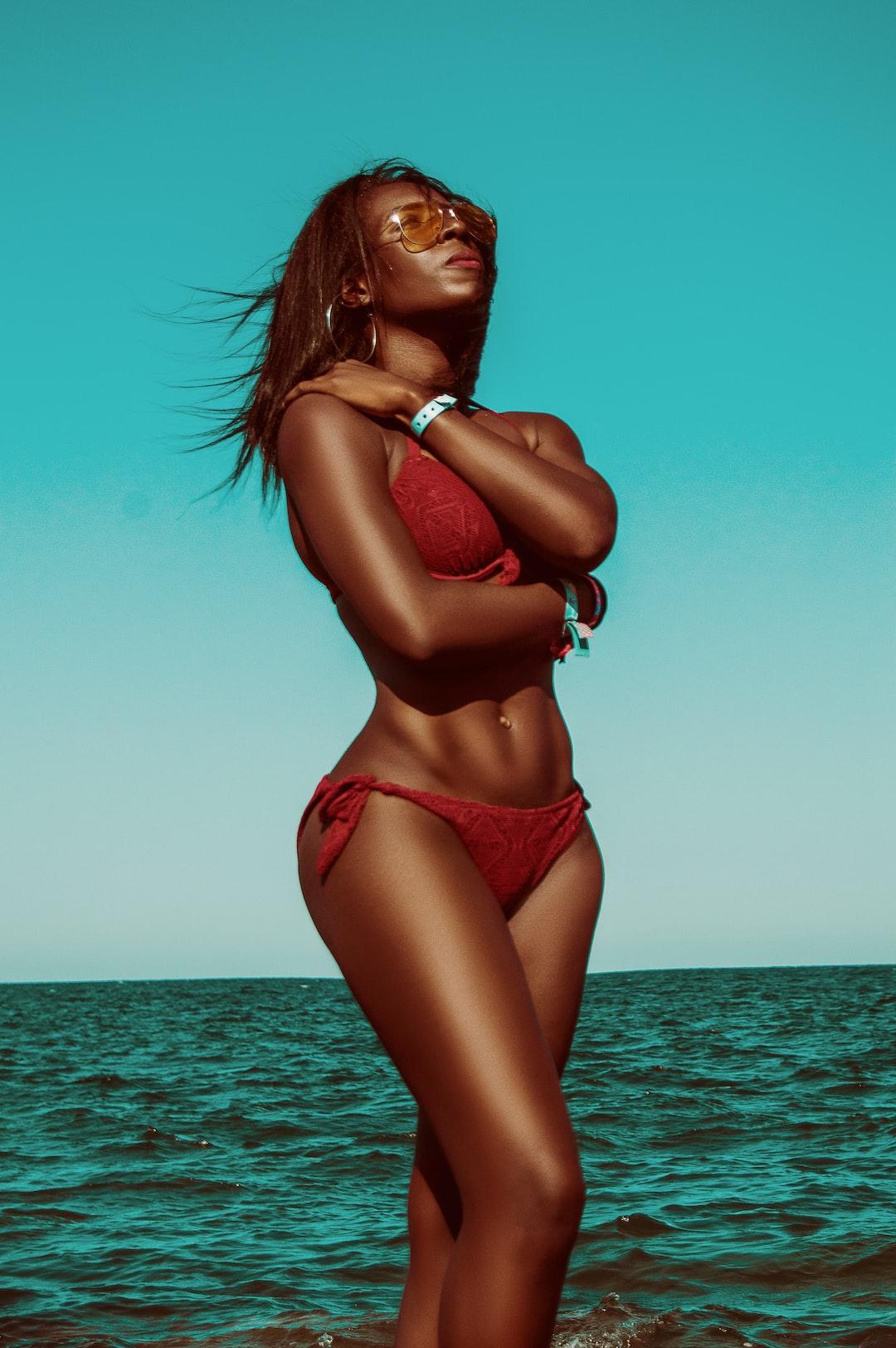 Beautiful summer fashion portrait of a gorgeous black model wearing a red bikini .