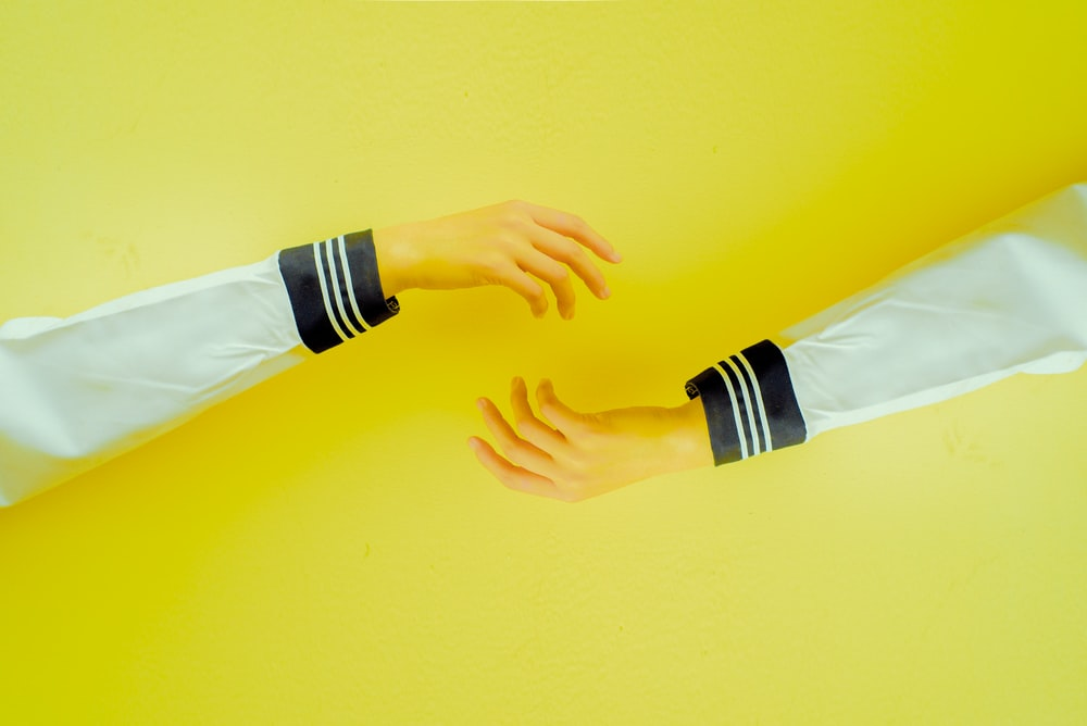 two hands reaching each other on yellow background
