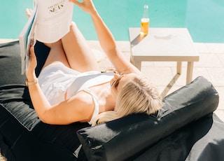 woman reading magazine while lying black lounge near swimming pool during daytime