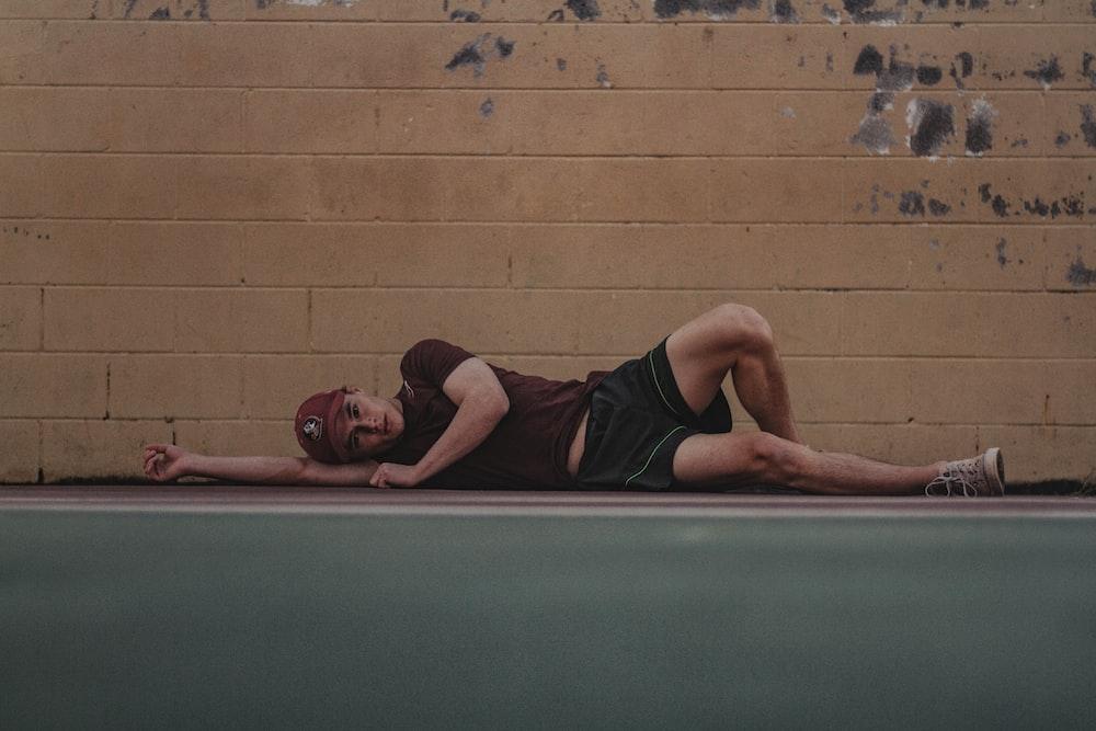 man lies on sidewalk near wall