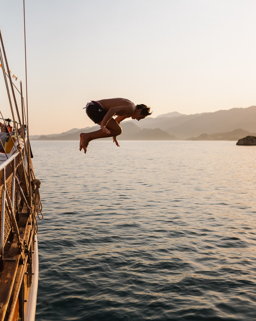 man jump over sea during daytime
