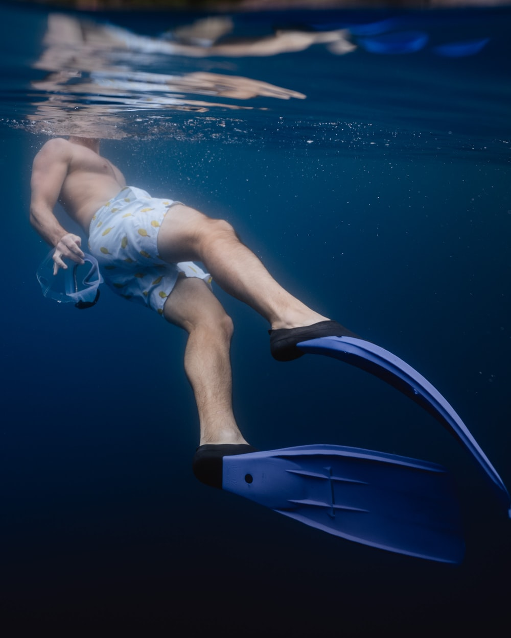 under water photography of man wearing blue flippers