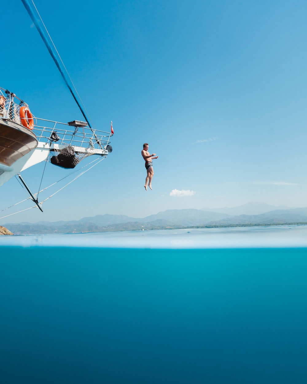 topless man jumping from boat viewing mountain during daytime