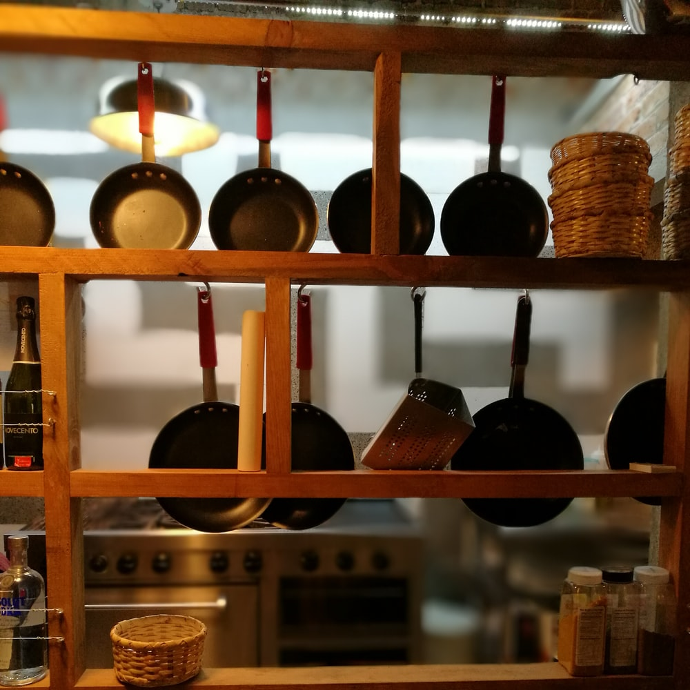 frying pans hanging on wooden rack
