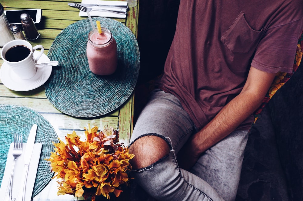 flat-lay photography of man sitting beside mug of smoothie and cup of coffee