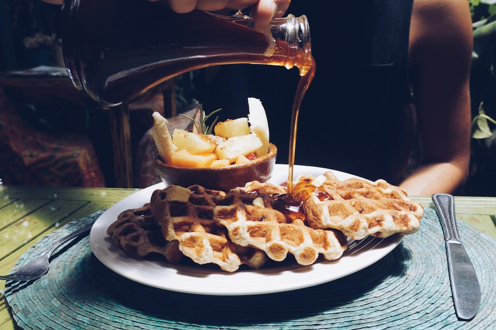 person poring syrup on waffles
