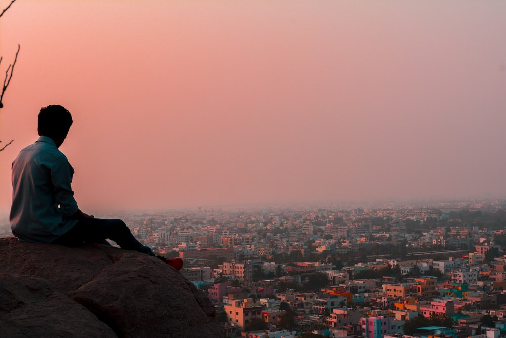 man sitting on rock formation facing on buildings during daytime