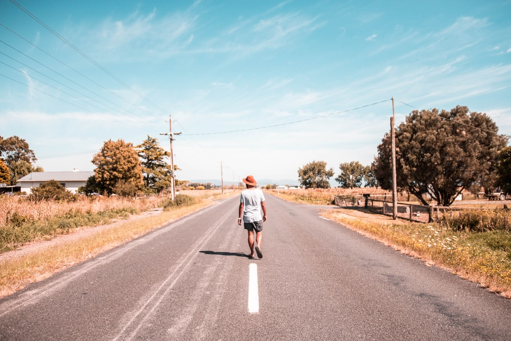 person walking on a road under blue sky during daytime
