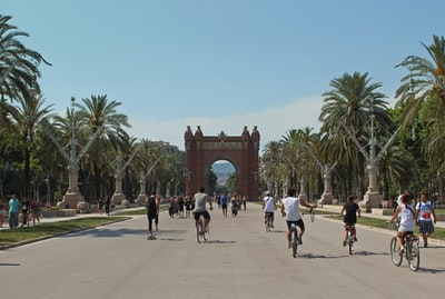 people running and riding bicycles on cement barcelona teams background