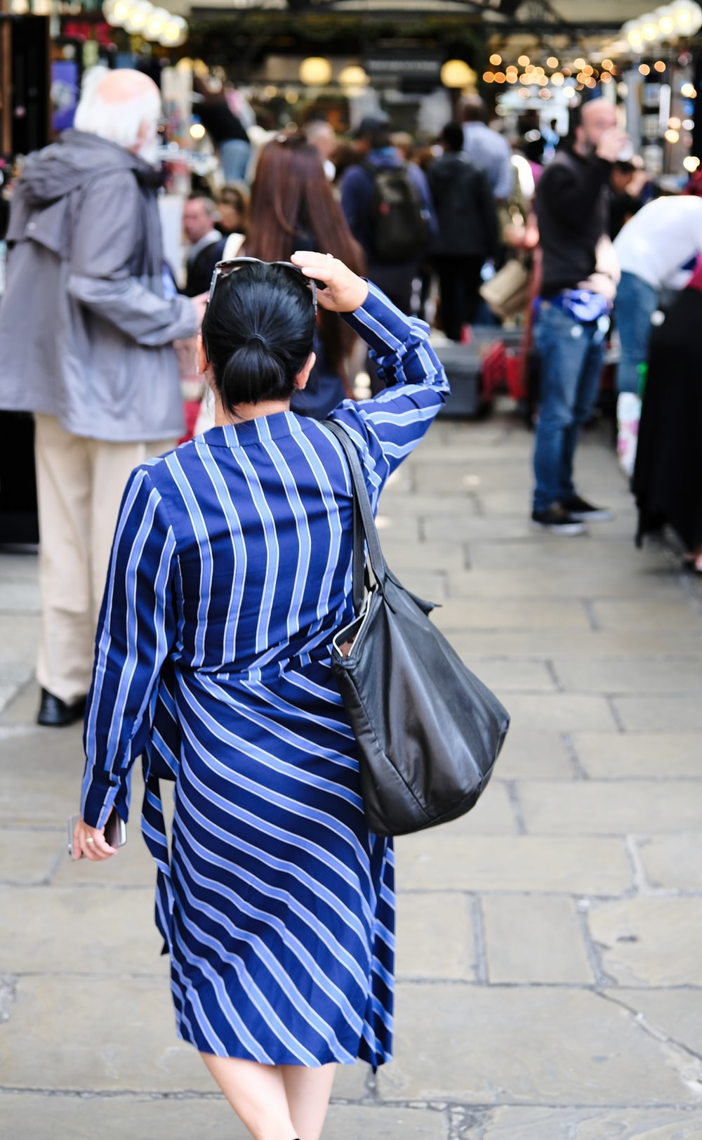 woman in striped dress walking near building