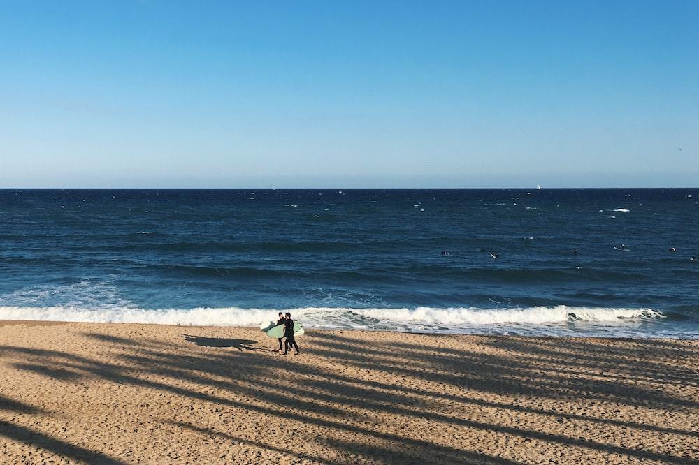 person walking beside seashore during daytime