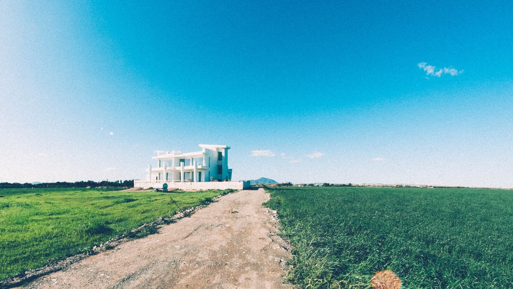 white concrete house surrounded by grass field under clear sky