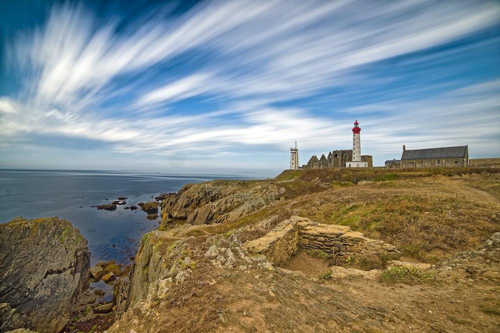 lighthouse under cloudy sky near cliff