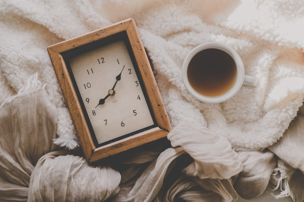 cup of coffee beside rectangular desk clock displays 8:08