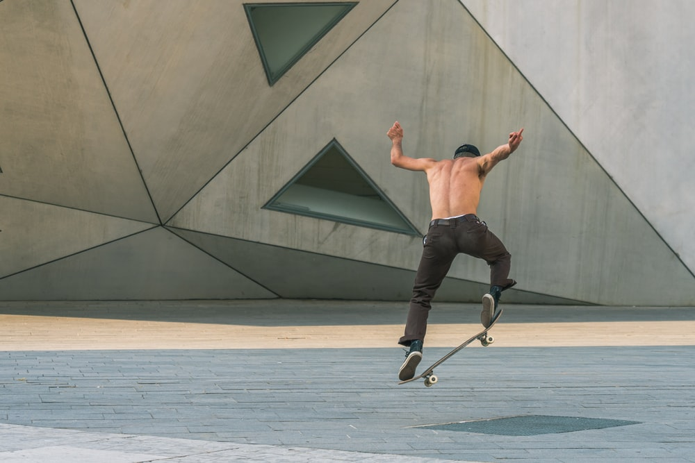 man doing tricks on a skateboard in mid air