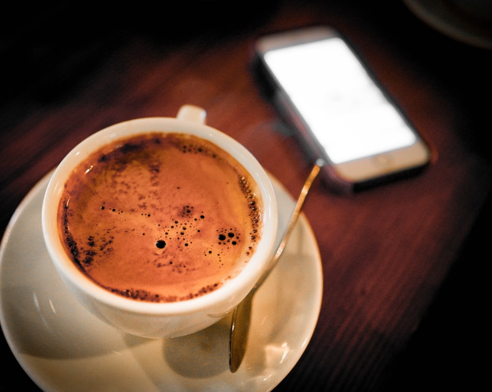 cup of coffee on saucer beside smartphone