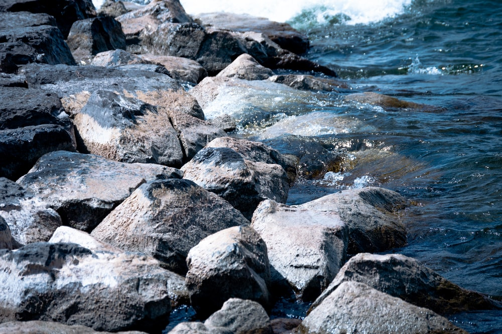 grey stone on body of water during daytime