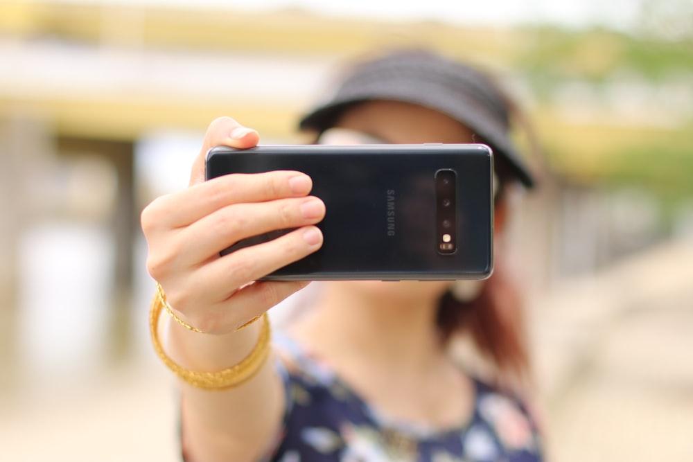 woman showing black Samsung smartphone