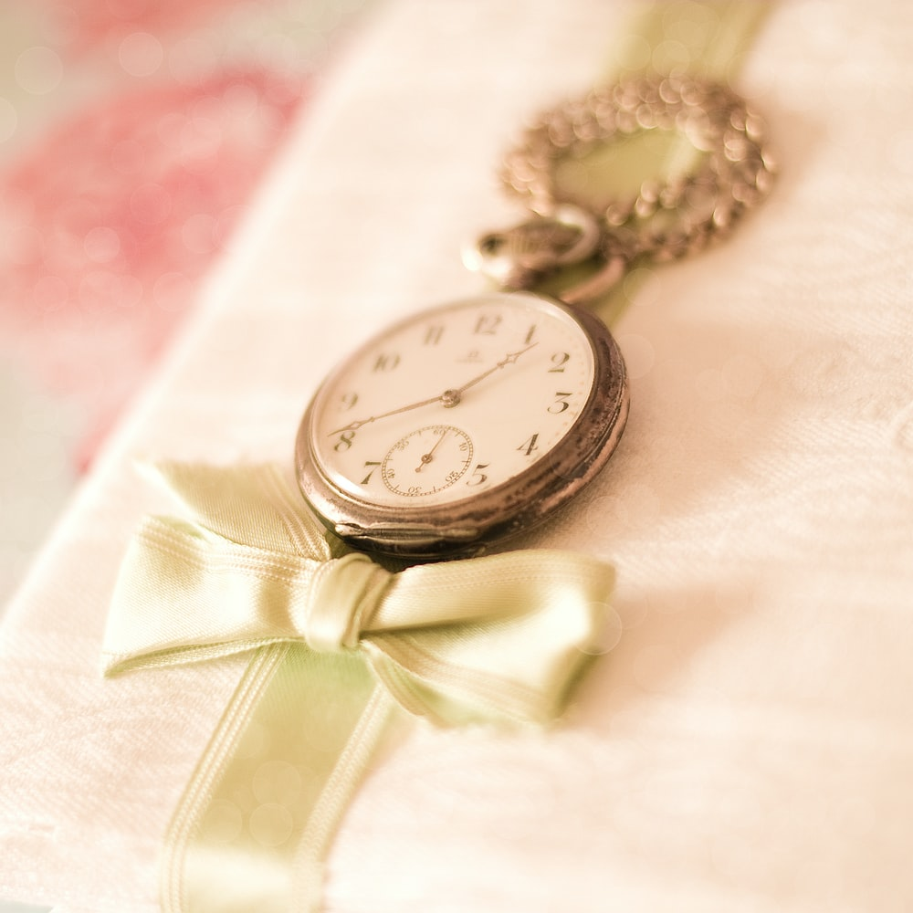 silver-colored pocket watch on white surface