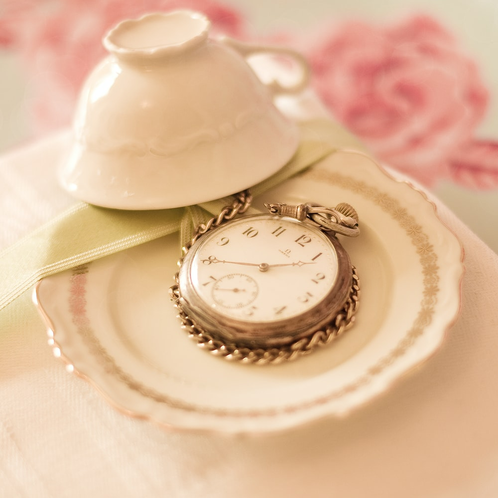 silver-color pocket watch near white teacup