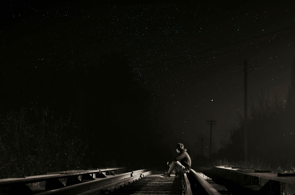 person sitting on railroad at night