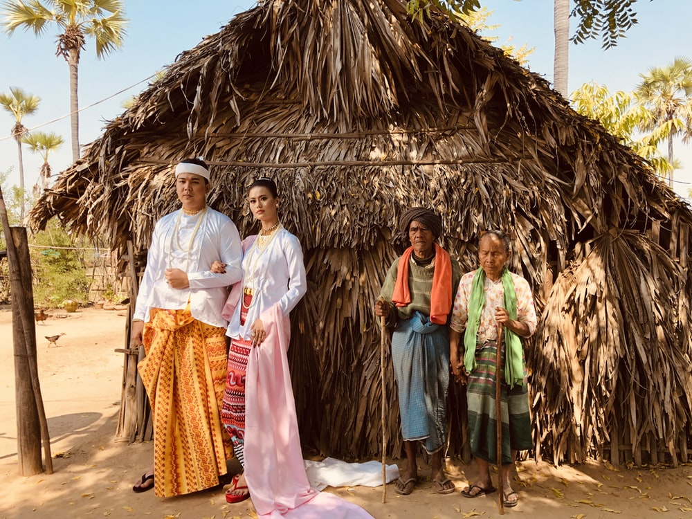 man and woman standing near another old man and woman beside straw house