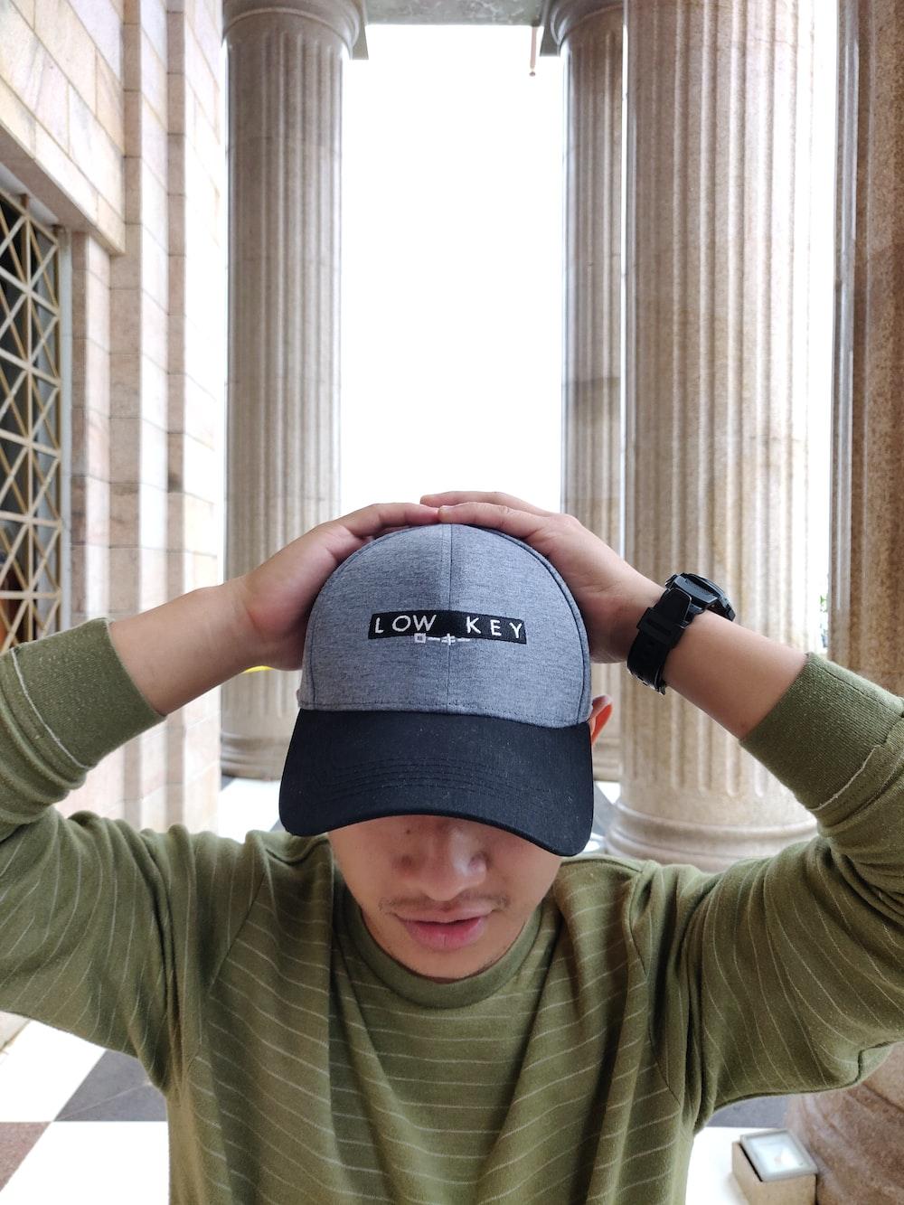 man holding his cap