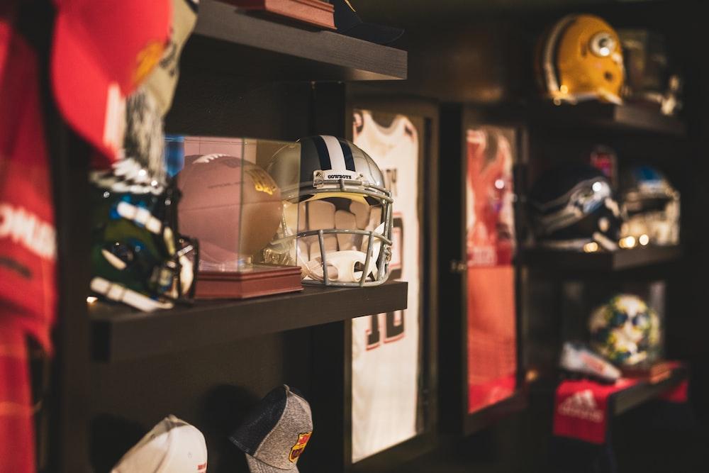 brown football and gray helmet on brown rack