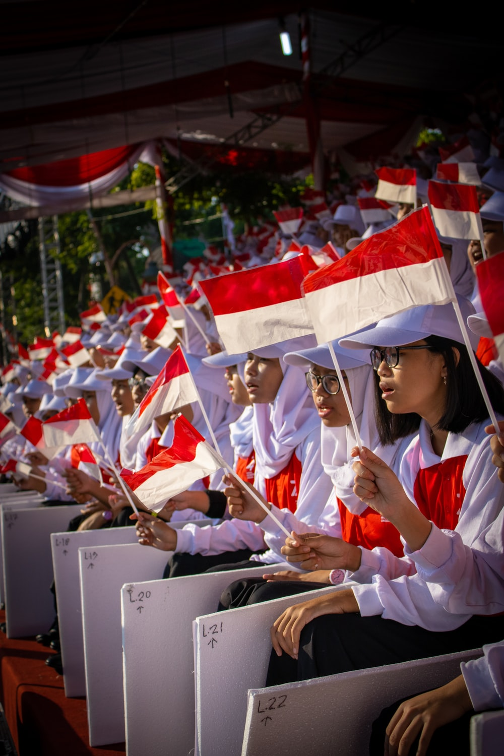 shallow focus photo of people holding Indonesia flag