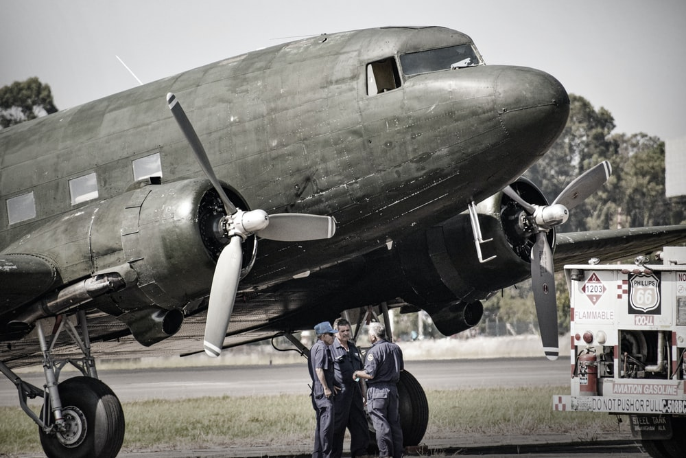grayscale photography of three men standing beside airplane