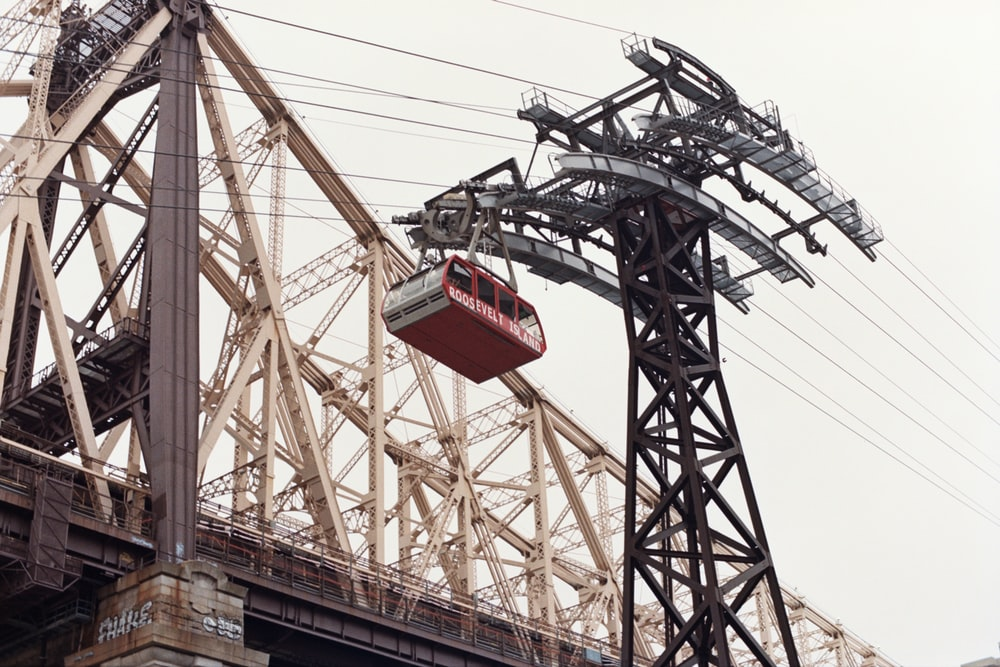 gray metal tower beside bridge during daytime