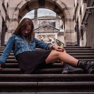 woman wearing blue denim jacket sitting on stairs