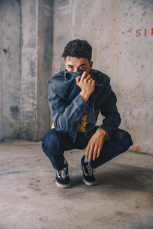 man wearing blue denim jacket and jeans