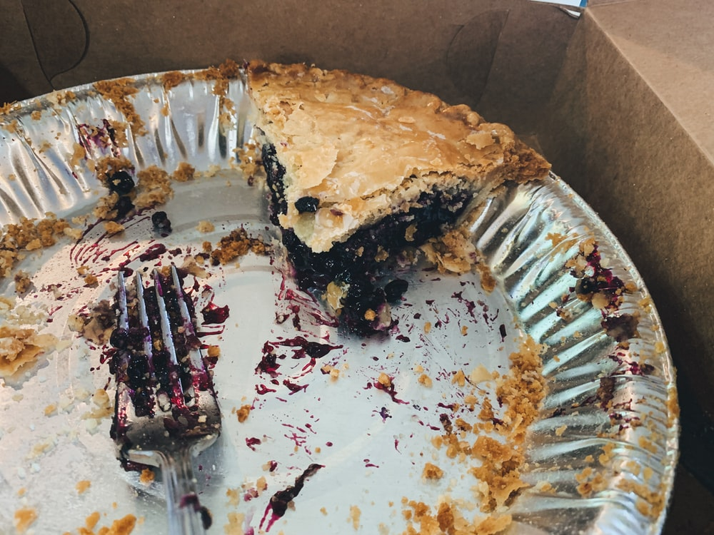one sliced pie left in tray near gray stainless steel fork