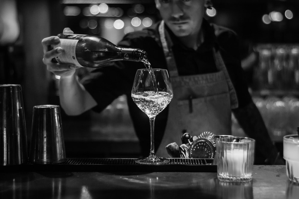 grayscale photo of bartender pouring liquid in wine glass