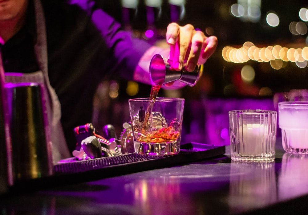 person pouring liquor in clear drinking glass