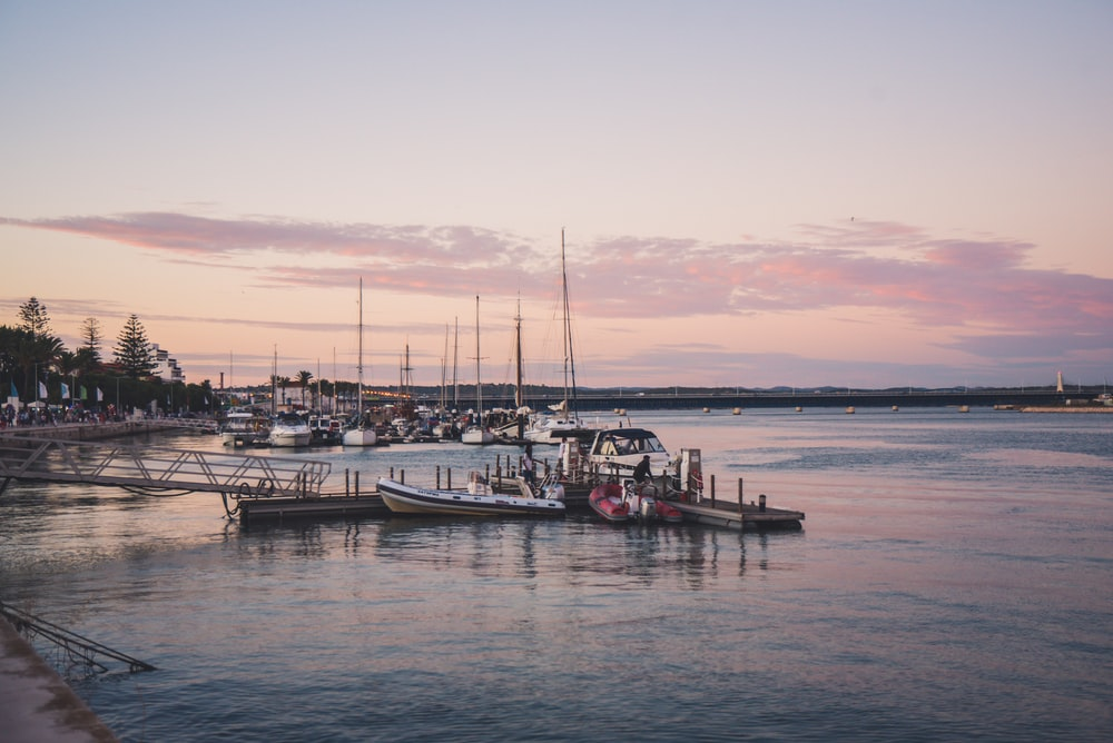 whit boat near wooden dock under gray sky