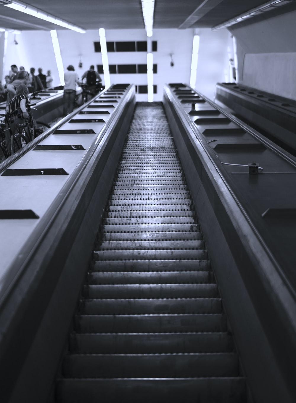 grayscale photography of people in escalator inside building