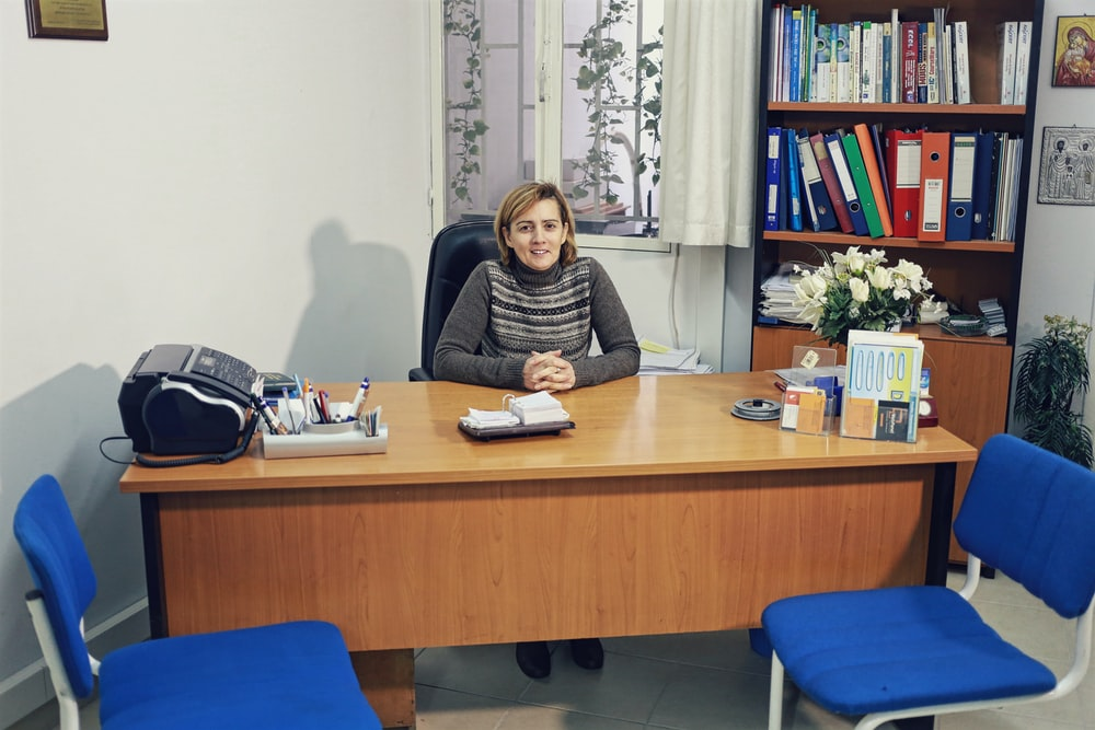 woman sitting beside desk near bookcase with books