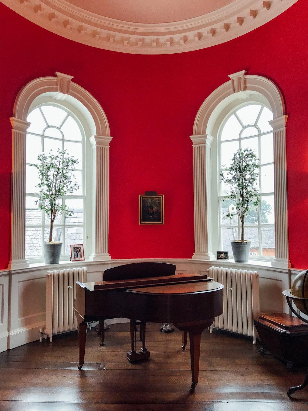 brown grand piano near windows