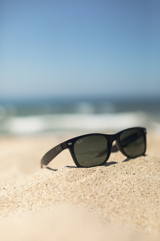 black wayfarer-style sunglasses on sand