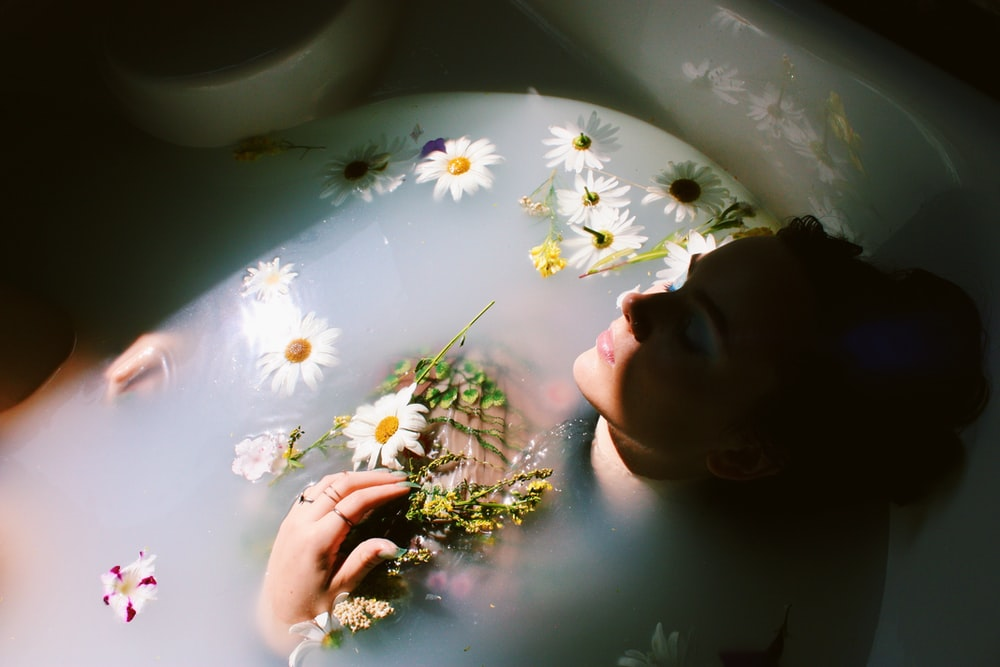 woman sitting in bathtub with white and yellow daisy flowers