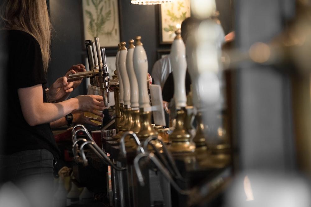 woman holding cup beside beer tap handles