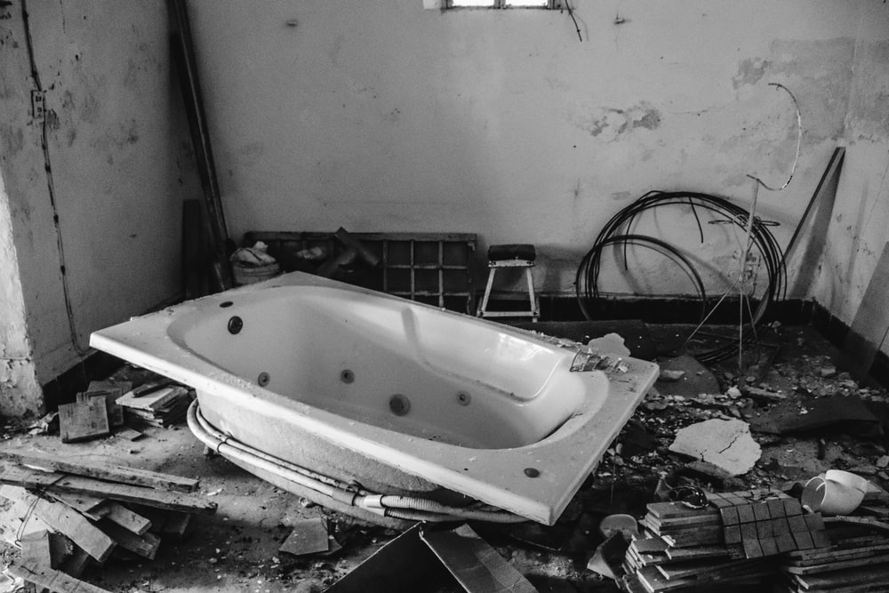 white bathtub inside room with scattered woods